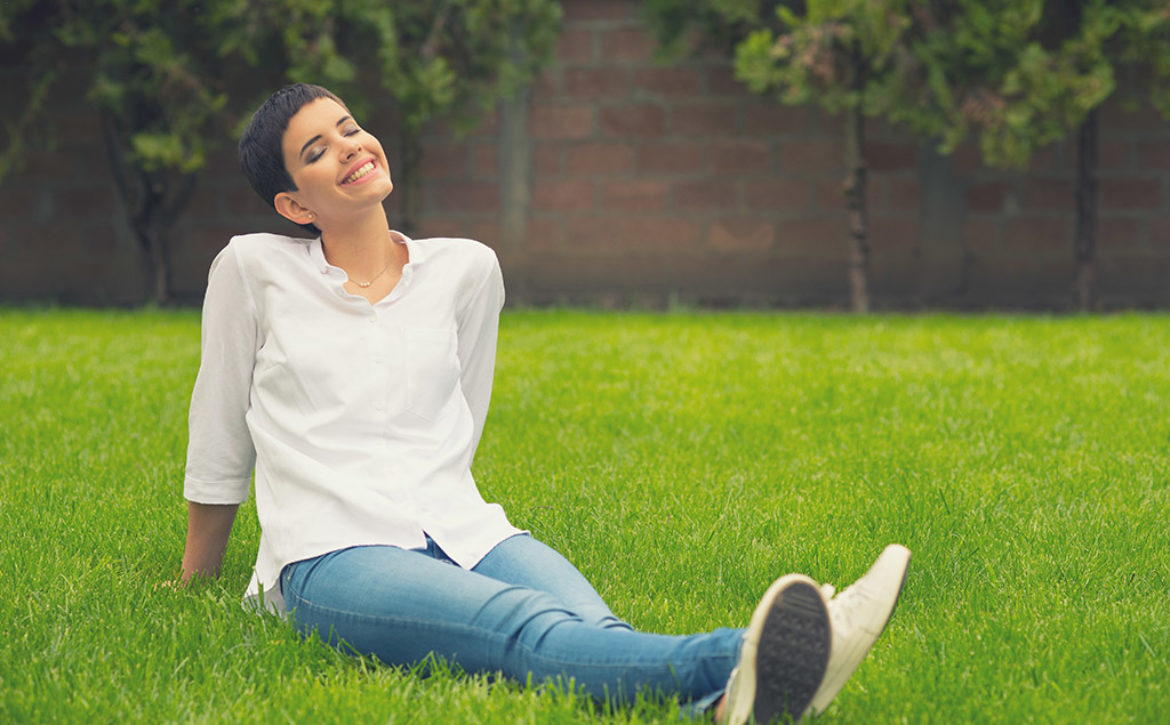 Beautiful smiling girl sitting on the grass of home garden on su