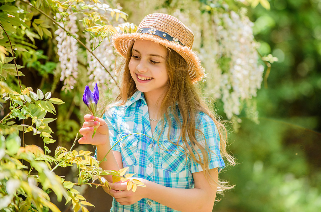 florist. Spring holiday. Womens day. Natural beauty. Childhood happiness. happy child hold iris flower. summer vacation. Green environment. little girl and iris flower. Living in the moment